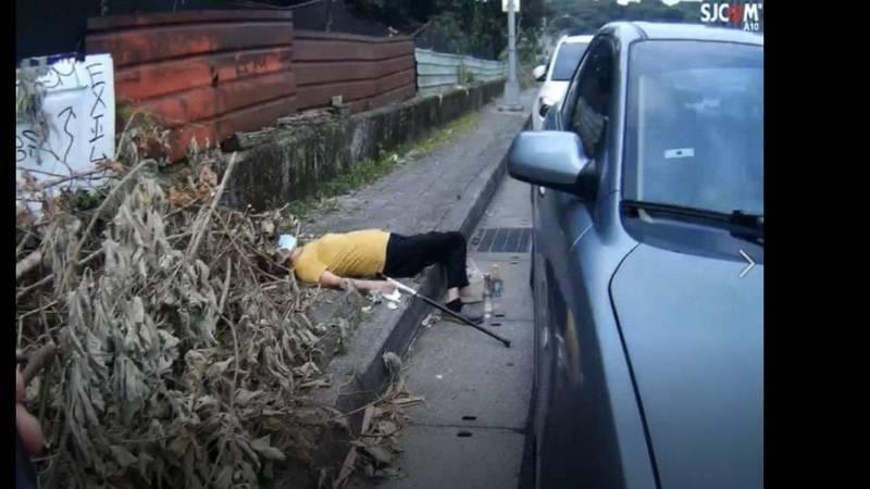 新北市汐止區環東引道旁人行道,今天一大清早赫見有人戴著口罩躺在雜草堆一動也不動,嚇壞路人。(記者林嘉東翻攝)