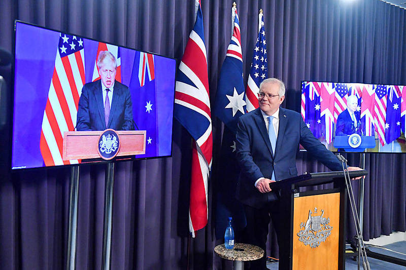 Australian Prime Minister Scott Morrison, center, attends a virtual news conference with British Prime Minister Boris Johnson, left, and US President Joe Biden at Parliament House in Canberra yesterday. Photo: EPA-EFE