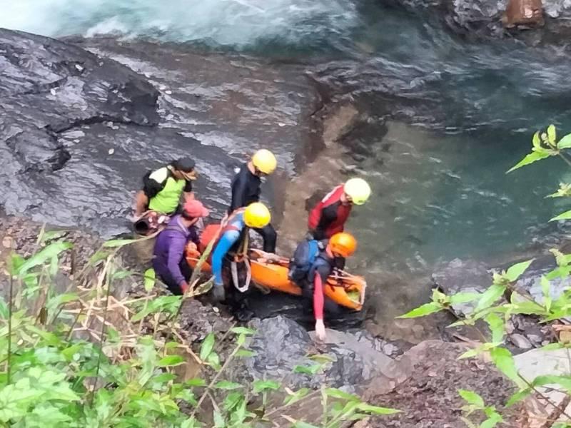新竹縣消防局等救難人員以捲式擔架把祈男抬離溪谷。(新竹縣消防局提供)