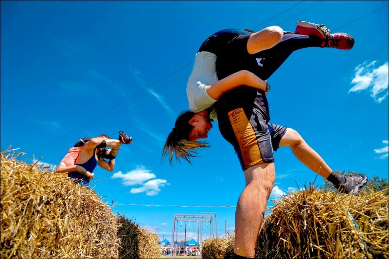 匈牙利背老婆大賽冠軍賽的男性參賽者,八月七日用傳統頭上腳下招式扛著另一半,在匈國塔皮歐比奇凱村跋涉。(路透)