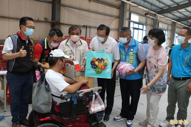 新北市副市長劉和然(右4)、淡水區弱勢關懷協會理事長蔡錦賢(左3)等人捐贈物資給家戶。(記者周湘芸攝)