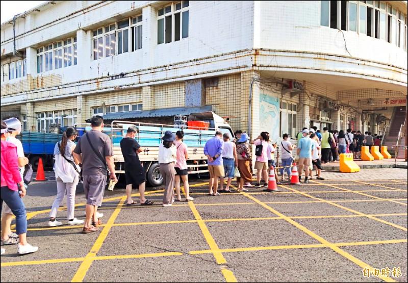 連假首日,竹圍漁港湧現採買人潮,民眾大排長龍等候進入魚貨直銷中心。(記者鄭淑婷攝)