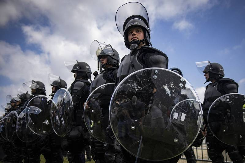 全副武裝的員警18日部署在國會大廈前,嚴防「為1月6日討公道」示威演變成暴亂。(彭博社)