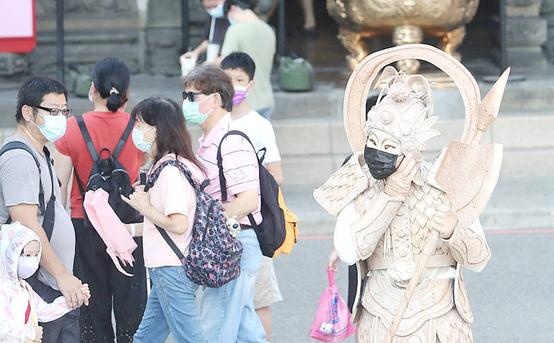A street performer puts on a mask to meet disease prevention requirements before beginning a performance in Taipei yesterday. Photo: CNA