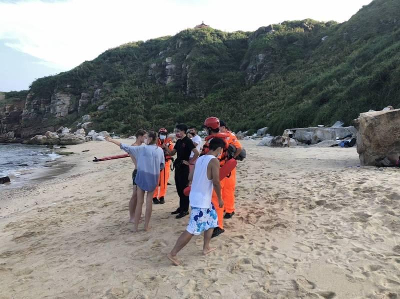 在岸上的兩名外籍遊客向搜救人員指出友人游泳的方向。(記者吳昇儒翻攝)