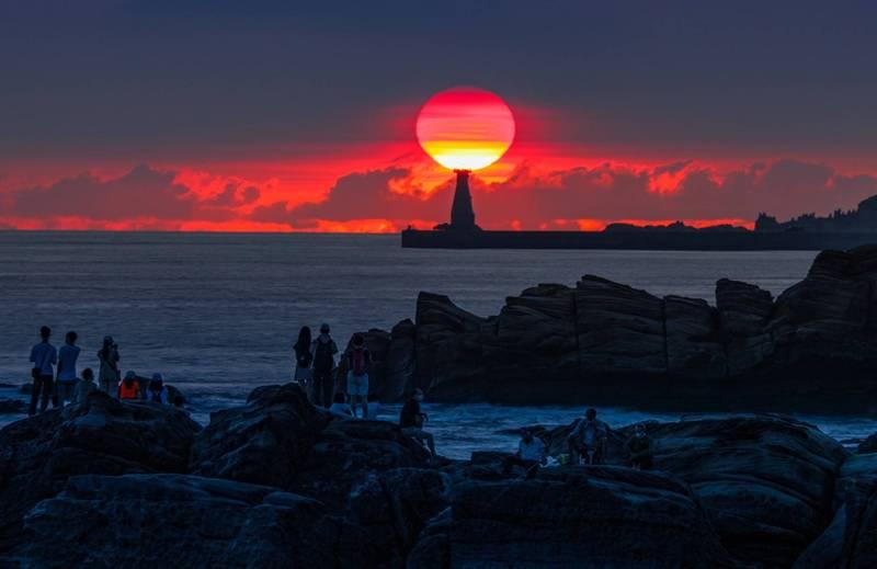 基隆外木山是攝影玩家追逐拍攝日出的勝地,中秋節前後從基隆外木山海岸,可以看到太陽從基隆港外堤燈塔後方升起,形成絕美的國門燈塔懸日。(圖為攝影師張隆提供)