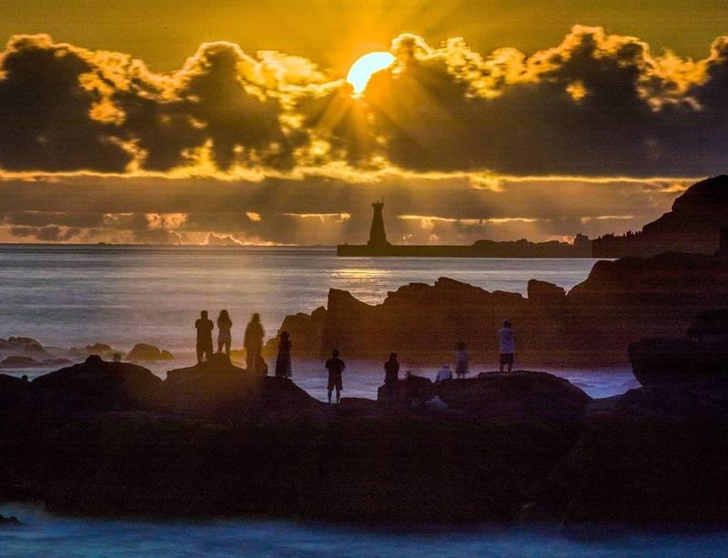 基隆外木山是攝影玩家追逐拍攝日出的勝地,中秋節前後從基隆外木山海岸,可以看到太陽從基隆港外堤燈塔後方升起;圖為太陽已經從燈塔升起,鑽入上方的雲層,霞光萬丈美不勝收。(圖為攝影師張隆提供)
