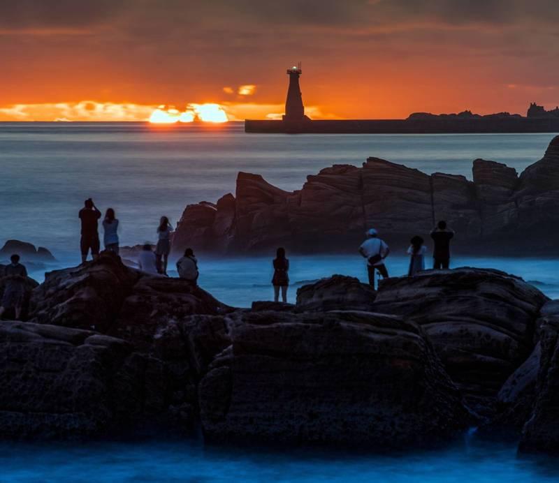基隆外木山是攝影玩家追逐拍攝日出的勝地,中秋節前後從基隆外木山海岸,可以看到太陽從基隆港外堤燈塔後方升起;圖為太陽正準備從海平面冉冉升起。(圖為攝影師張隆提供)