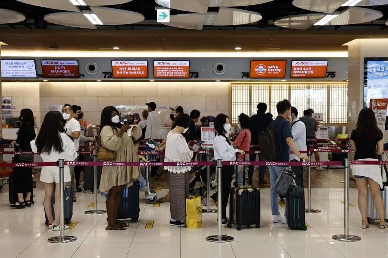 南韓中秋假期出現旅遊潮,知名景點濟州島估計遊客總數將達到20萬人,衝擊當地的檢疫能量。南韓金浦機場濟州航空櫃檯示意圖。(彭博)