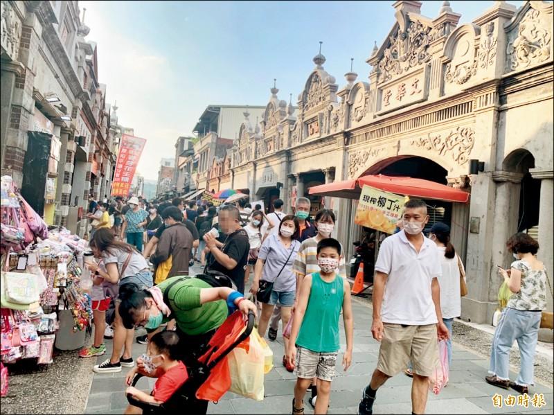 天氣太熱、口罩太悶?走在大溪老街就有遊客當街拉下口罩邊走邊喝,求個消暑涼快。(記者李容萍攝)