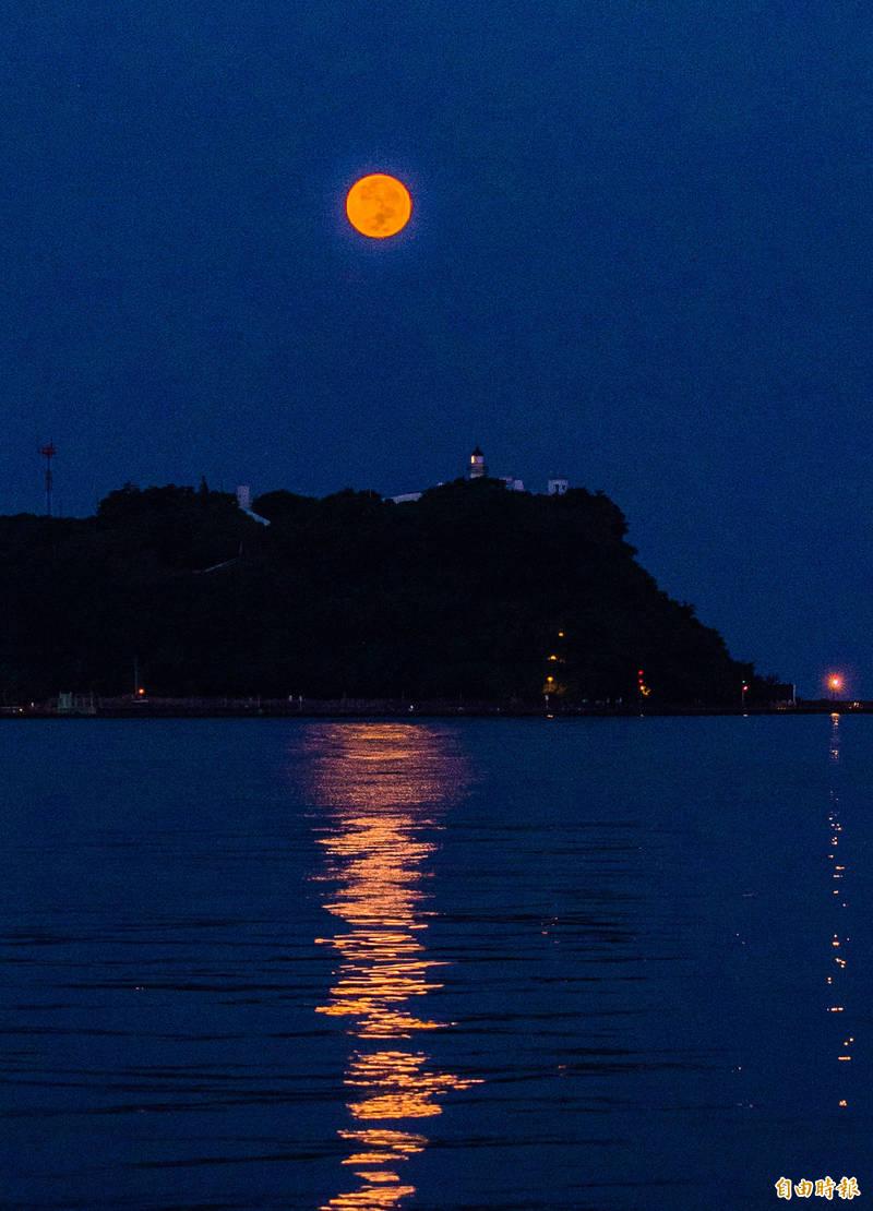 月到中秋分外明,今天是中秋節,今天清晨月沒時,月亮落入海平面時的軌跡會經過高雄旗津燈塔正後方。(記者張忠義攝)