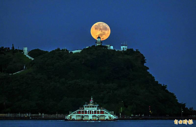 今天是中秋節,今天清晨月沒時,月亮軌跡剛好落在高雄旗津燈塔正後方,出現美麗又難得一見的「燈塔懸月」。(記者張忠義攝)