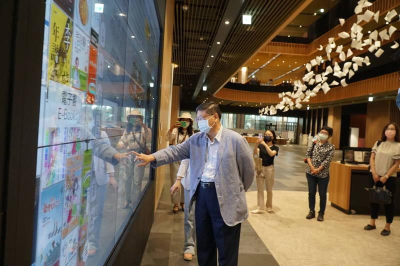 新竹縣長楊文科體驗台南市立總圖書館內的大型觸控螢幕搜尋資料。(圖由縣府提供)