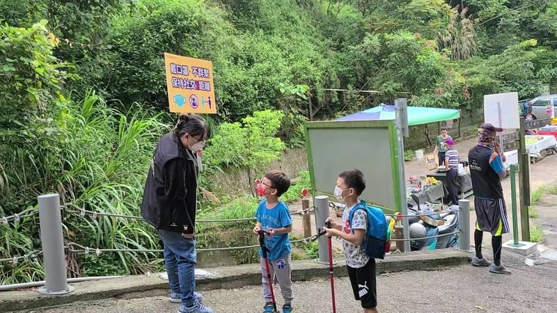台中市「觀光景點疏導隊」到風景區加強宣導防疫,小朋友好奇駐足聆聽。(觀旅局提供)