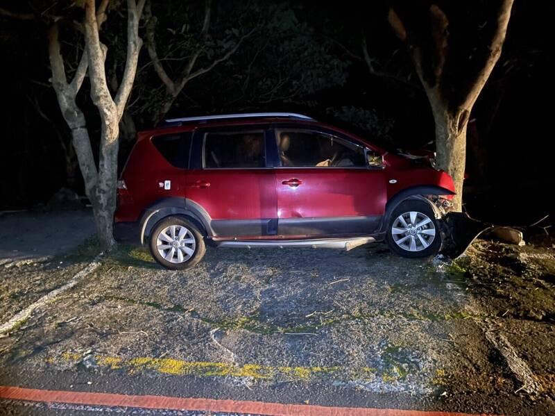 自小客車撞上路樹後,直接卡在2樹中央,幸運沒有摔落山下。(警方提供)