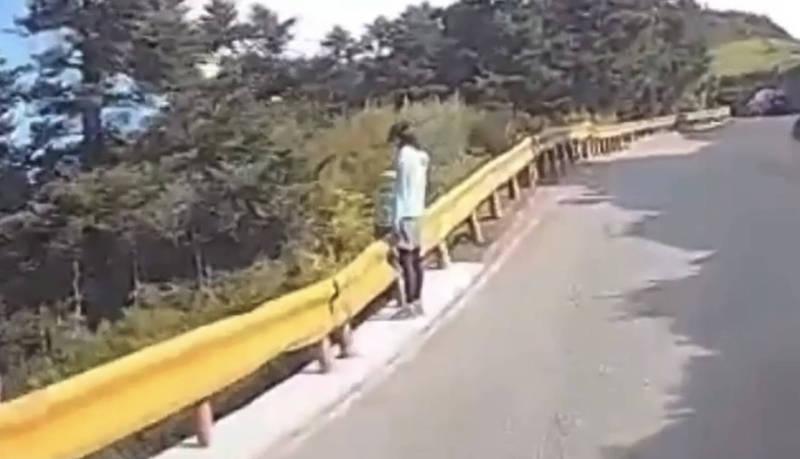 熱心駕駛的行車記錄器拍到婦人摔出護欄外,女兒站在護欄邊。(圖擷自爆料公社)