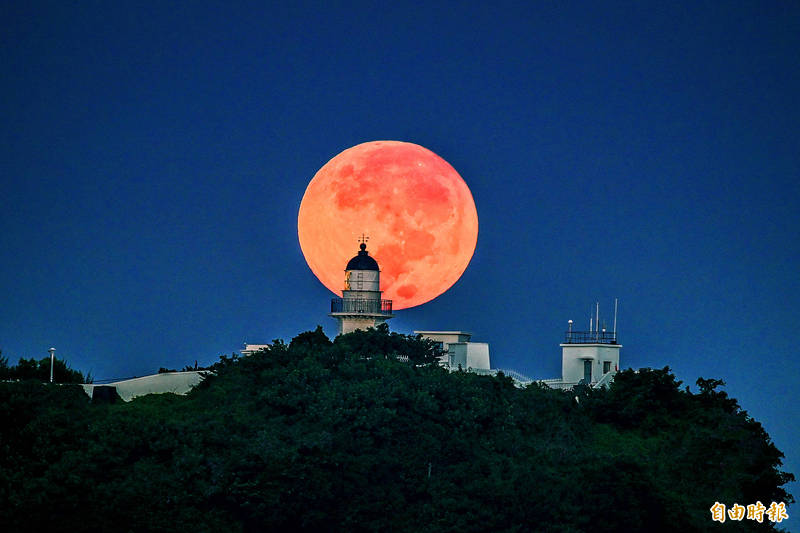 The moon sets behind the Kaohsiung Lighthouse in Cijin District on the Mid-Autumn Festival yesterday morning. Photo: Chang Chung-yi, Taipei Times