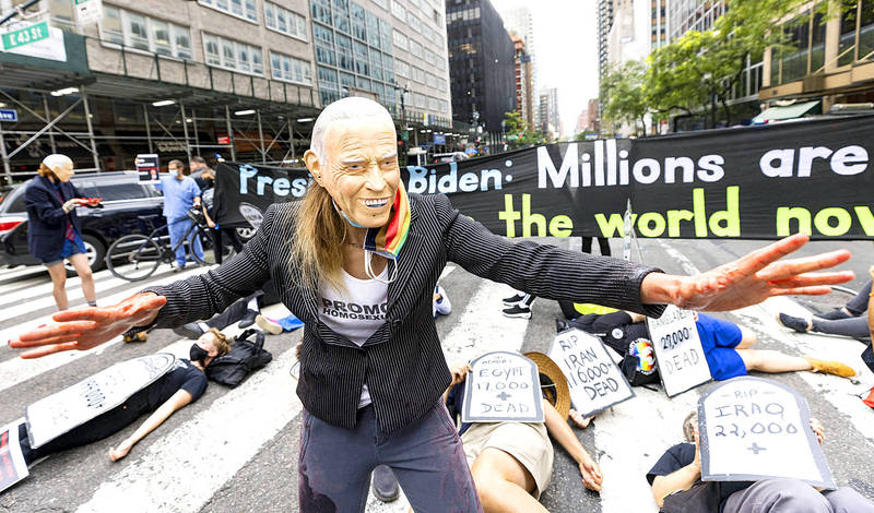 """A protester in a mask depicting US President Joe Biden looks on as people hold a """"die-in"""" and block New York City's 2nd Avenue during a rally on Sunday near the UN headquarters calling on Biden and the international community to help provide wider access to COVID-19 vaccines. Photo: EPA-EFE"""