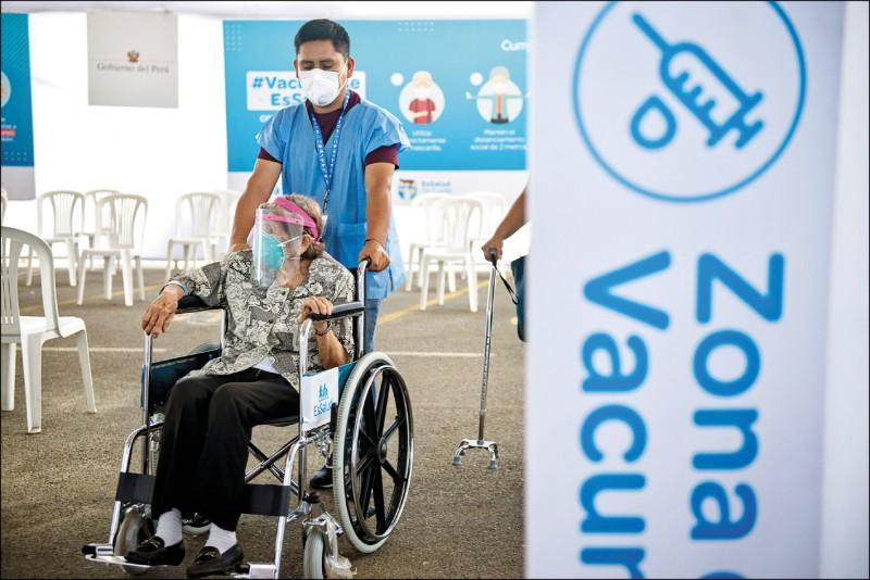 秘魯醫療工作人員3月在利馬一處疫苗接種站,推著一名坐著輪椅的老婦去接種疫苗。(彭博檔案照)