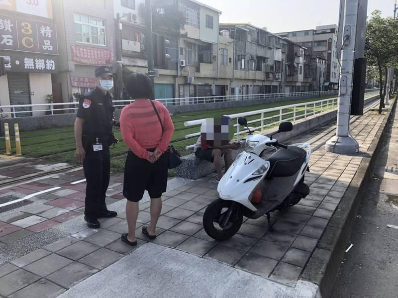陳姓母子將故障機車停在輕軌旁人行道、呆坐路旁,高雄捷警主動上前了解。(記者王榮祥翻攝)