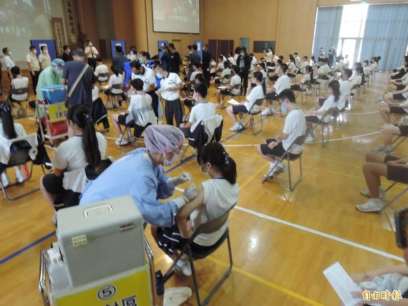 台南慈濟高中BNT疫苗首日開打,現場採宇美町打法,學生坐著不動,由醫護人員移動逐一施打。(記者蔡文居攝)