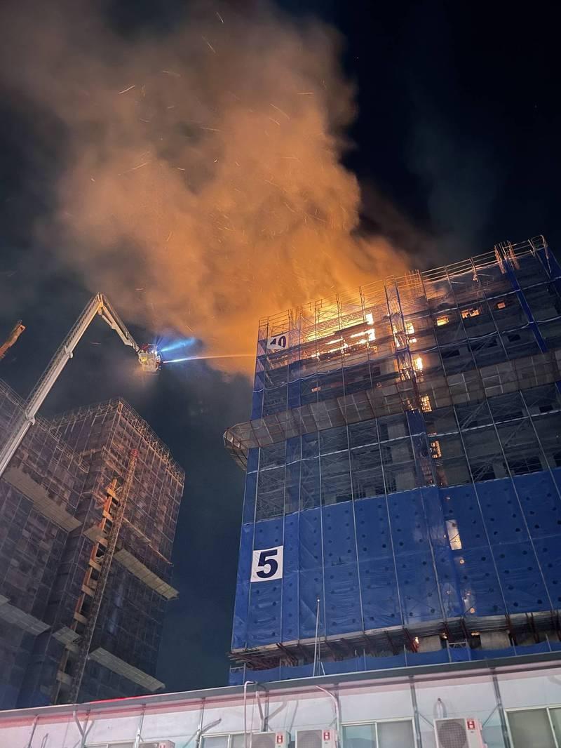 北市信義區興建中的公共住宅暗夜竄火舌,消防局派員灌救,半小時後撲滅火勢,未有傷亡。(記者邱俊福翻攝)