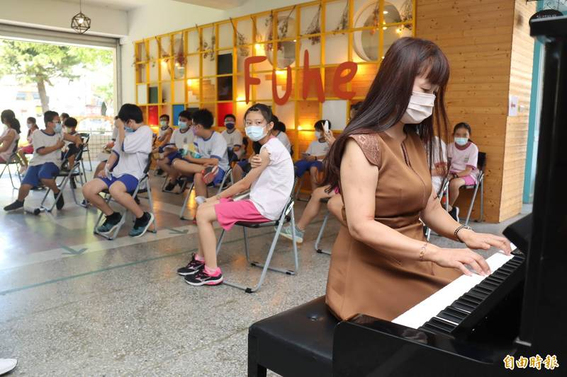 校長范筱蓉在接種學生的留置觀察區彈鋼琴,為學生紓緩情緒。(記者翁聿煌攝)