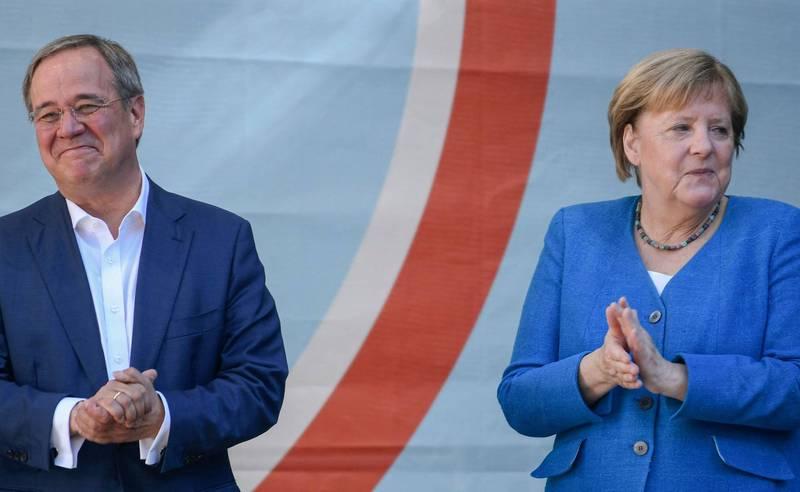 總理梅克爾(右)今天幫同黨總理候選人拉謝特(左)拉票。(法新社)