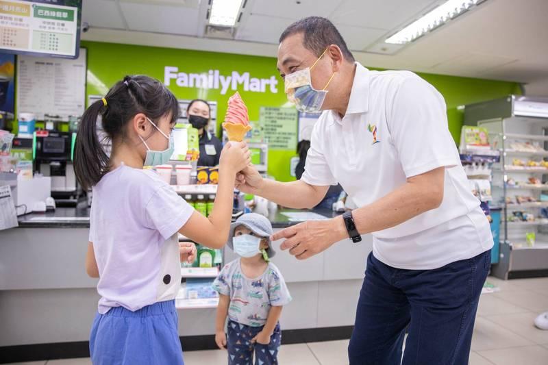 新北市長侯友宜(右)與小朋友分享霜淇淋,象徵聖火傳遞精神。(圖由新北市政府提供)