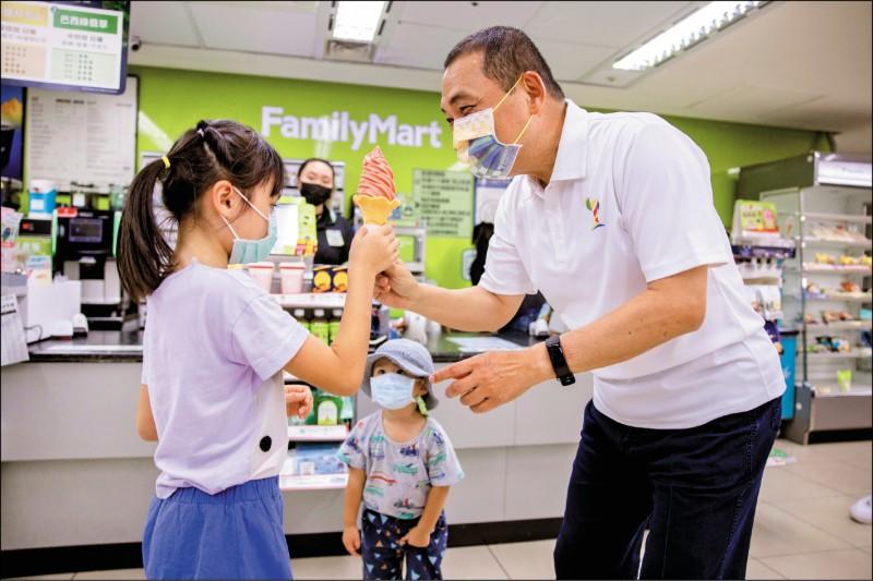 新北市長侯友宜(右)與小朋友分享霜淇淋,象徵聖火傳遞精神。(新北市政府提供)