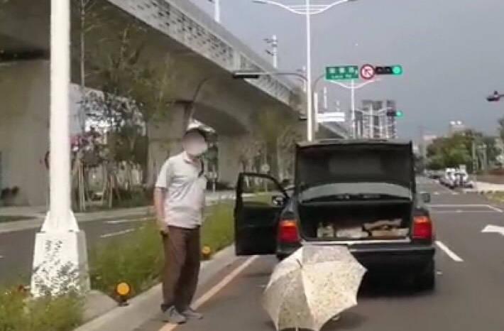 老翁開車途中車子突然拋錨,只有一把雨傘充當警示牌。(記者許國楨翻攝)