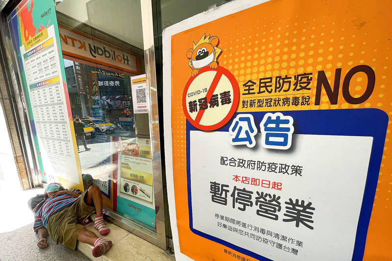 A homeless person yesterday sleeps on the sidewalk outside a branch of the Holiday KTV chain in Taipei, which has been closed amid a nationwide level 2 COVID-19 alert. Photo: CNA