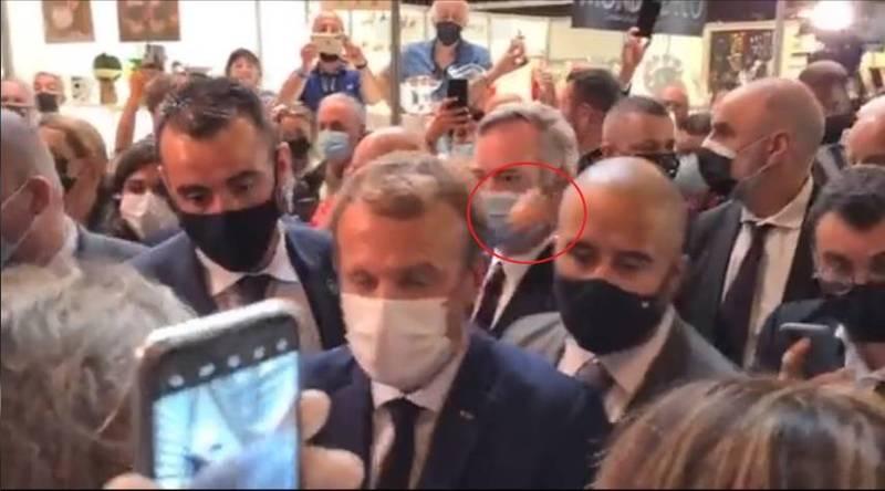 法國總統馬克宏今日在里昂遭抗議份子丟雞蛋(紅圈處)。(擷取自推特)