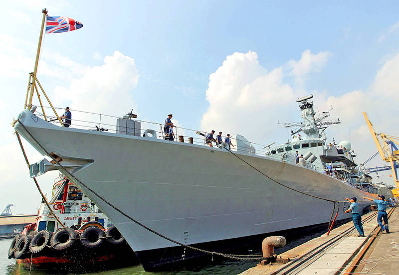 Two members of the Indonesian Navy, right, help the HMS Richmond dock at Tanjung Priok Port in Jakarta on May 22, 2011. Photo: EPA
