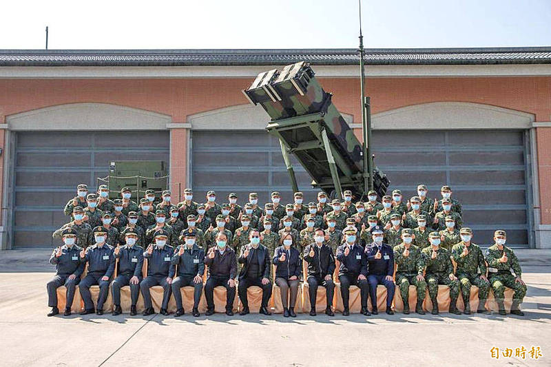 President Tsai Ing-wen, front row eighth right, and soldiers from the Defense and Artillery Command's Taichung branch pose in front of a Patriot Advanced Capability-3 missile system on Sept. 10. Photo copied by Wu Shu-wei, Taipei Times