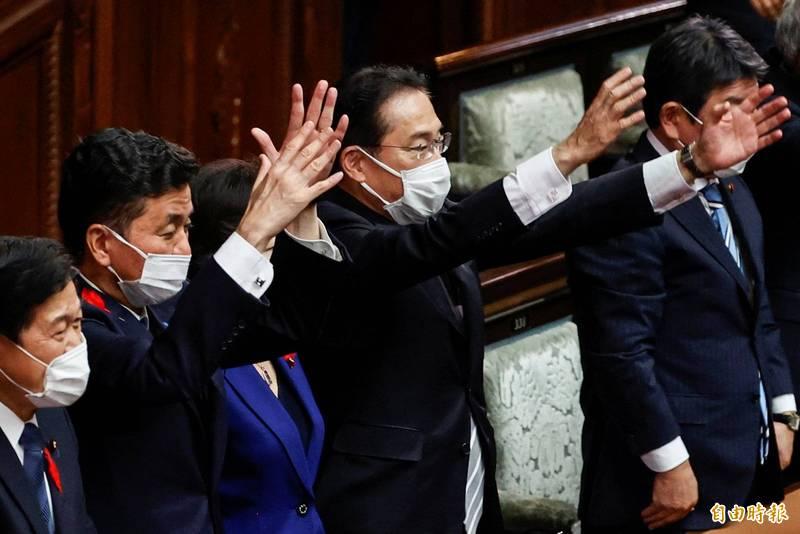 日本東京議會宣布下議院解散後,日本首相和執政的自民黨領導人岸田文雄及其內閣部長舉手高呼「萬歲」。(路透)