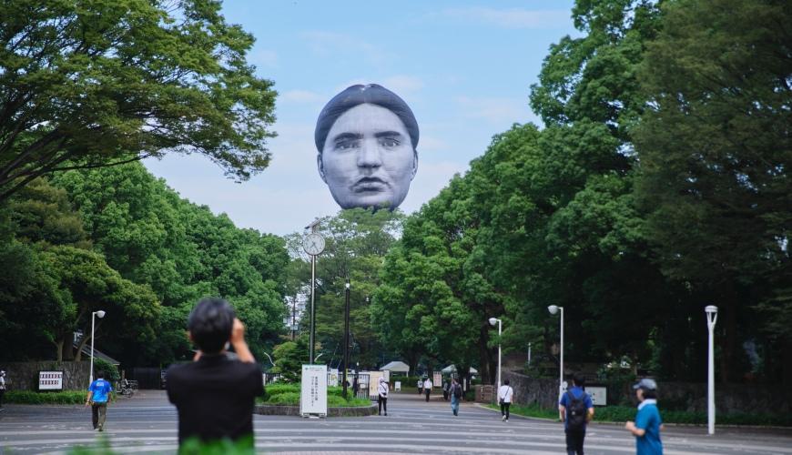 東京上空浮現「詭異巨人頭」 6層樓高裝置藝術竟與東奧有關聯?