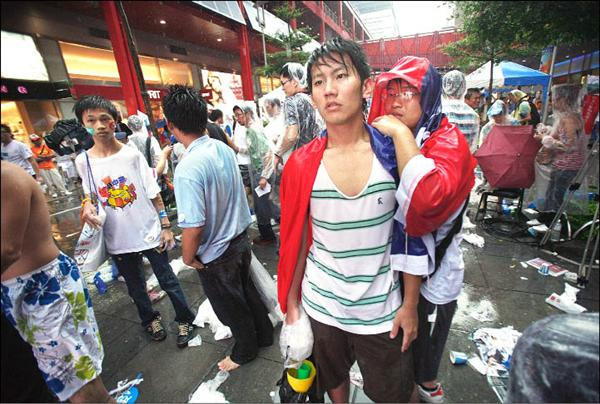 午後的一陣大雨,讓所有在戶外大螢幕看到台灣隊史上首度敗給中國隊的球迷,更顯得落寞。(美聯社)