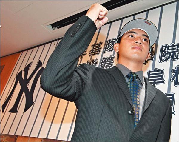 在與洋基簽約的記者會上,郭阜林舉起握拳的右手,表現在大聯盟打拚的信心。(記者詹朝陽攝)