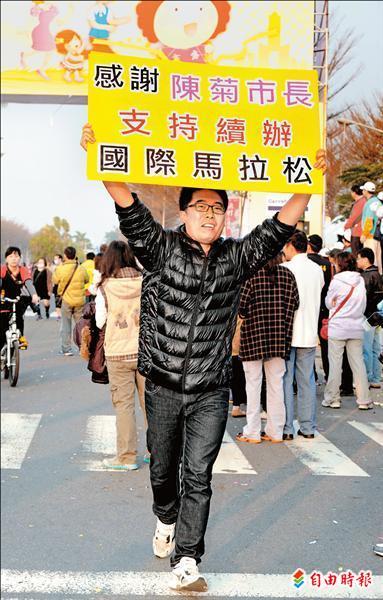 有跑者高舉感謝陳菊市長支持續辦國際馬拉松的標語。(記者張忠義攝)