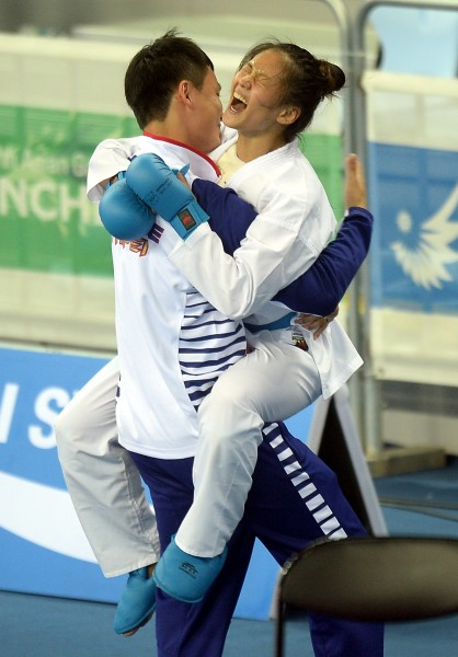 文姿云〈右〉擊敗哈薩克對手,拿下金牌後,激動得跳到教練身上相擁慶祝(記者林正堃攝)