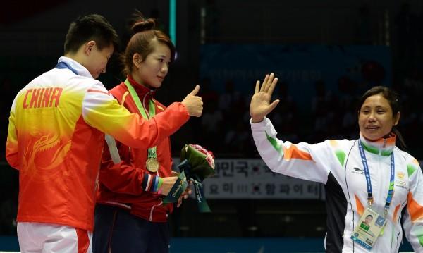 在離場前,中國金牌選手尹軍花豎起大拇指向德薇致意,德薇此時才略有笑意揮手離開。(法新社)