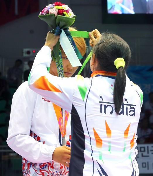 德薇將自己的銅牌套在南韓選手的脖子上。(法新社)
