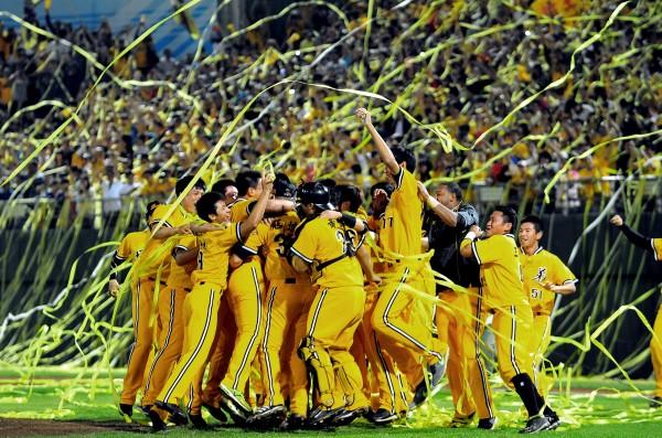 兄弟球迷拋下黃色彩帶,和球員一起慶祝拿下下半季冠軍。(記者林正堃攝)