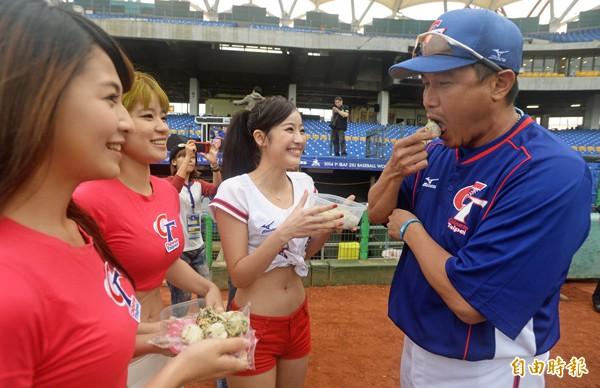 棒球甜心賽前送上「淘汰郎飯糰」,總教練郭李建夫(右)吃掉後,果然順利淘汰日本隊拿下冠軍。(記者林正堃攝)