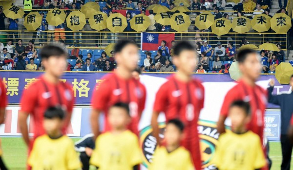 台灣球迷昨在台、港足球賽上高舉黃傘,傘上寫著「風雨中抱緊自由、自信可改變未來」。(圖擷自《港足冰室》臉書專頁)