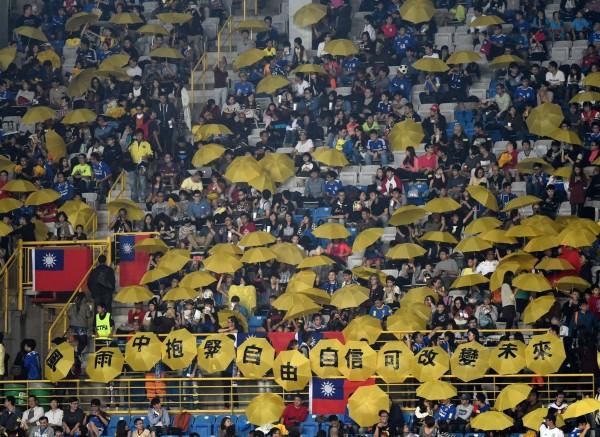 台灣球迷昨在台、港足球賽上高舉黃傘,挺香港爭取真普選。(圖擷自《港足冰室》臉書專頁)