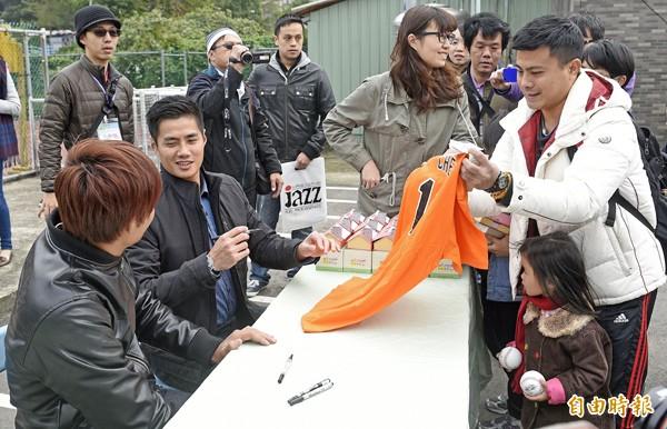 陳偉殷(左二)與王維中(左一)參加活動結束後,耐心親切地幫球迷簽名。(記者陳志曲攝)