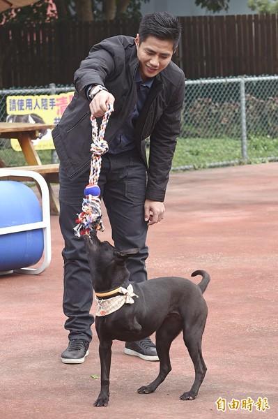 陳偉殷在戶外活動區拿起玩具開心逗弄小狗。(記者陳志曲攝)