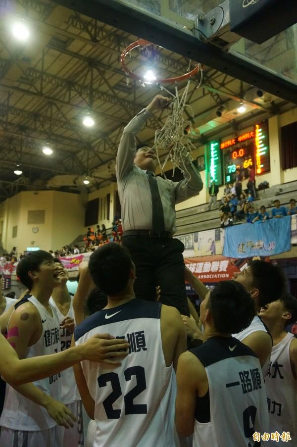 健行科大奪下甲二級冠軍,總教練劉孟竹剪下勝利籃網。(記者張正邦攝)